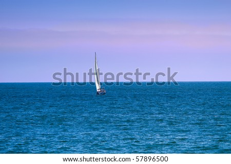 Sailboat on the ocean against dusk sky of blue and pink.
