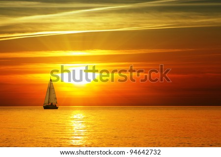 Sailboat on the ocean at sunset - stock photo