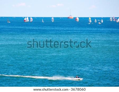 Sailboat race with speeding jetski in foreground - stock photo