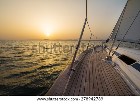 Sailboat sailing at sunset - stock photo