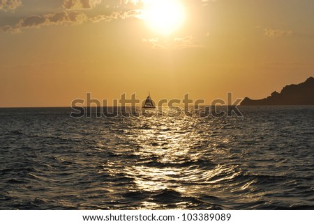 Sailboat sailing at sunset in the waters of Santorini Greece