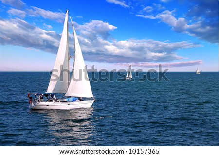 Sailboat sailing in the morning with blue cloudy sky - stock photo