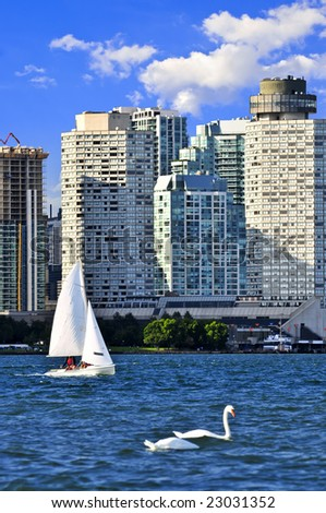 Sailboat sailing in Toronto harbour with scenic waterfront view - stock photo