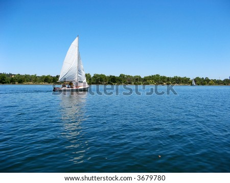 Sailboat sailing on early morning blue water river - stock photo