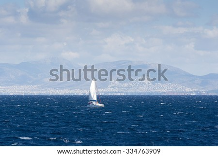 sailboat sailing ship in the Aegean sea. In the background the city of Athens is