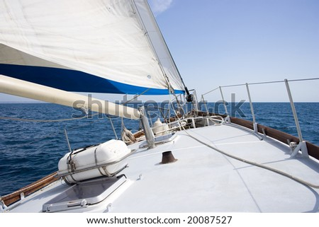 Sailboat sailing with gentle wind in the calm sea. - stock photo