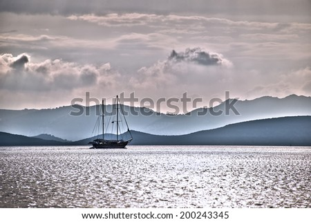 Sailboat silhouette in the sunset, Greek coast in the background