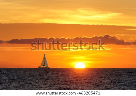 Sailboat sunset is a sailboat sailing along the water with a beautiful cloudscape in the background as the sun is going down on the ocean horizon.