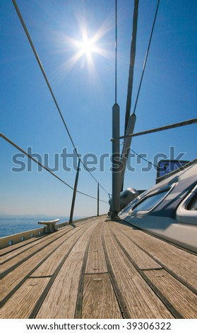 Sailboat with blue sky and sun - stock photo