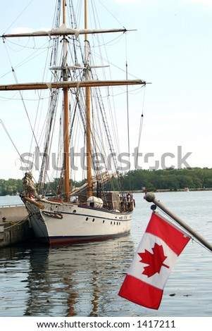 sailboat with Canadian flag in forefront - stock photo