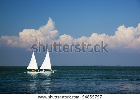 Sailboat with two sails on beautiful, sunny day. - stock photo