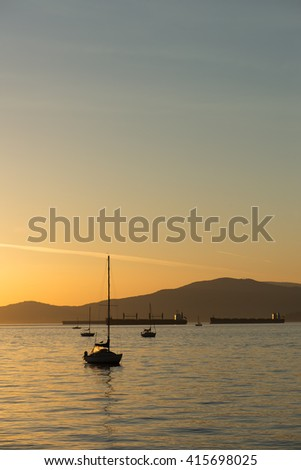 sailboats and freight ships at sunset in English Bay, Vancouver, BC. - stock photo