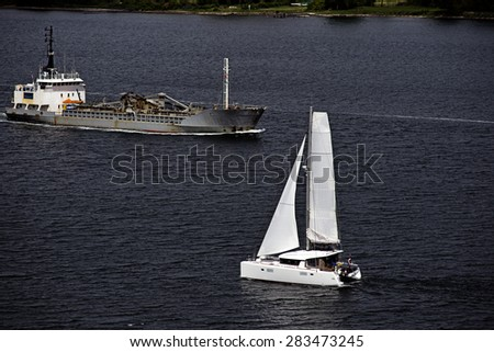 Sailboats and freighter on Little Belt close to Middelfart and Fredericia in Denmark - stock photo