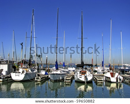 Sailboats and yachts in a quiet harbor ocean marina among other nautical vessels. - stock photo