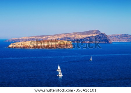 Sailboats at Santorini island's caldera, Greece - stock photo