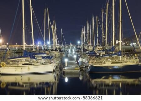 sailboats in the harbor at night - stock photo