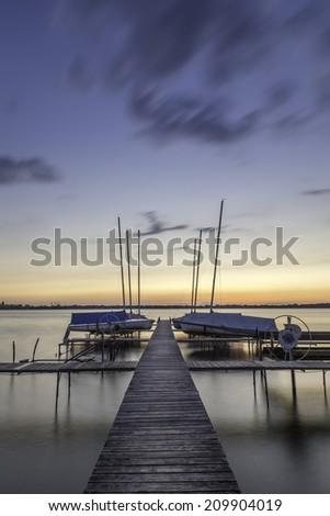 sailboats rest on lake monona at sunset - stock photo