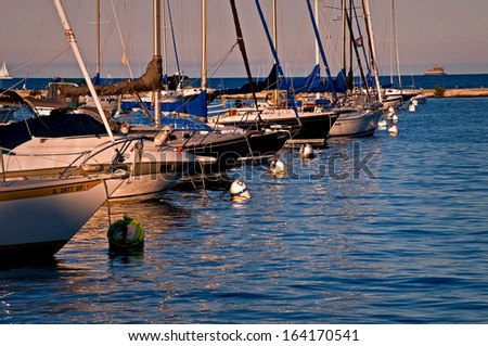 Sailboats rest peacefully at their moorings as the sun sets on Monroe Harbor, Chicago lakefront. - stock photo