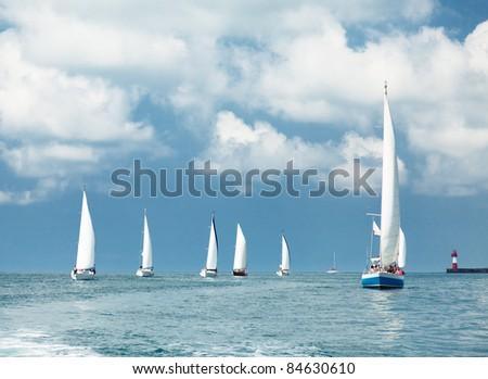 Sailboats sailing, blue cloudy sky and white sails - stock photo