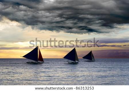 Sailboats under the stormy sky. - stock photo