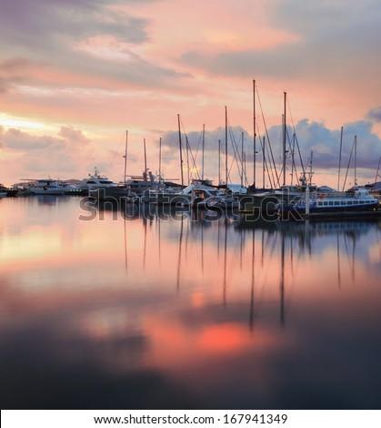 Sailboats with sunset reflection - stock photo