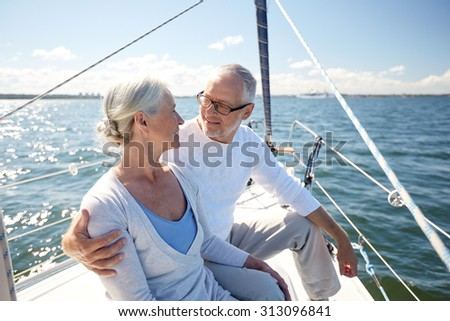 sailing, age, tourism, travel and people concept - happy senior couple hugging on sail boat or yacht deck floating in sea - stock photo