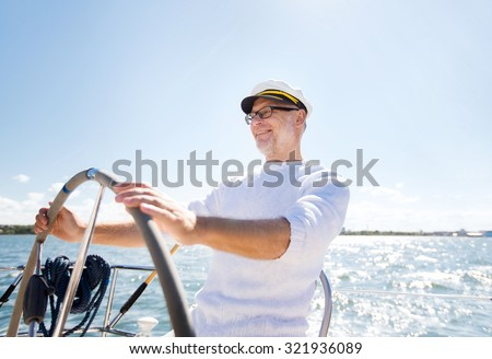 sailing, age, tourism, travel and people concept - happy senior man in captain hat on steering wheel and navigating sail boat or yacht floating in sea - stock photo