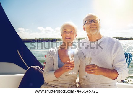 sailing, age, travel, holidays and people concept - happy senior couple with champagne glasses on sail boat or yacht deck floating in sea - stock photo
