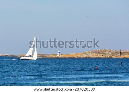 Sailing at sea into rocky archipelago  - stock photo