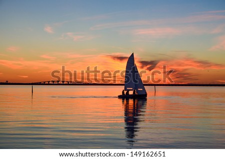 Sailing at sunset in front of the Oland bridge in the Baltic sea, Sweden - stock photo