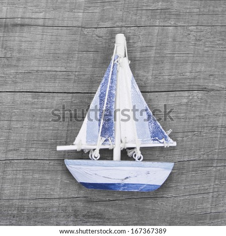 Sailing boat decoration on the wooden background - stock photo