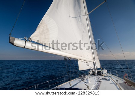 Sailing boat going fast on all sails in calm Mediterranean sea. Wide angle shot. - stock photo