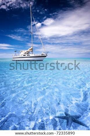 Sailing Boat in beautiful tropical lagoon with starfish in the foreground - stock photo