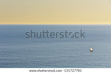Sailing boat in sailing into unknown. Beautifully colorful sky at sunset. - stock photo