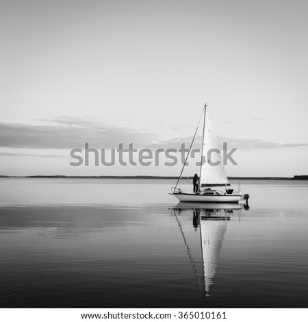 Sailing boat on a calm lake with reflection in the water. Serene scene landscape. Black and white square vintage photograph. - stock photo