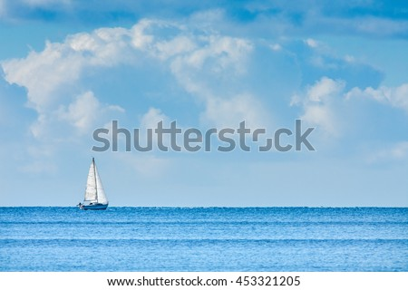 Sailing boat on Blue sea with big clouds. Conceptual image of uncertain future, isolation, solitude and loneliness.