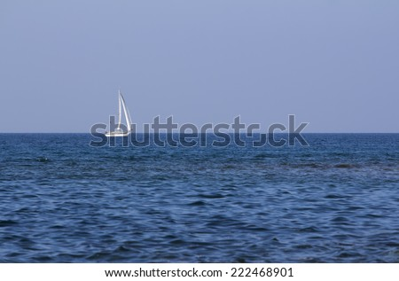 Sailing boat on the open blue sea at the sunset. - stock photo