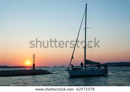 Sailing boat passing light beacon in sunset - stock photo