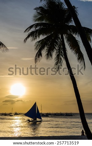Sailing boat under sail on the horizon and silhouette of people sitting and admiring of beautiful sunset under palm tree at tropical exotic white beach on Boracay, Philippines.