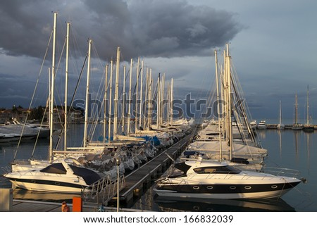 Sailing boats and yachts in a marina during the calm sunrise, against old Mediterranean town and cloudy sky before storm - stock photo