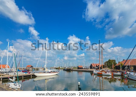 Sailing boats in the Dutch harbor of Hindeloopen on a sunny summer day - stock photo