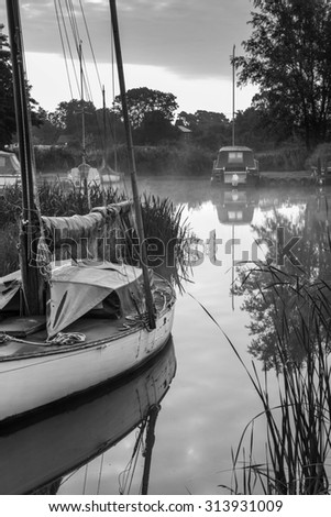 Sailing boats moored on riverbank at sunrise in countryside landscape in black and white - stock photo