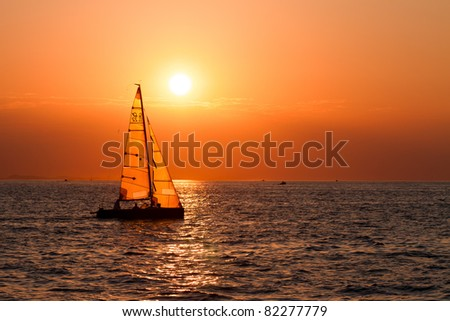 Sailing boats on a background of a beautiful sunset - stock photo