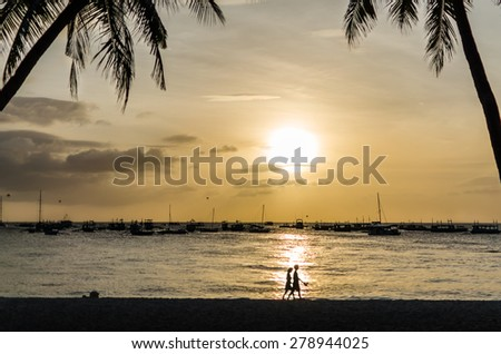 Sailing boats on the horizon and silhouette of lovely couple walking along tropical exotic beach with palm trees during beautiful sunset on Boracay, Philippines. - stock photo