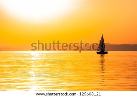 Sailing boats with a beautiful sunset at the sea - stock photo
