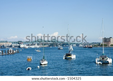 Sailing  boats with solar panels and oil tankers on St Charles River, Boston, Mass - stock photo