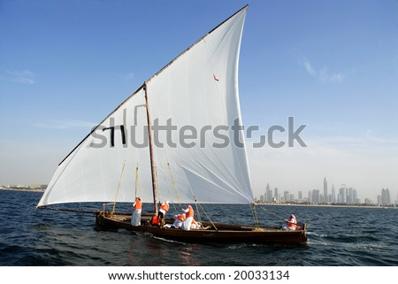 Sailing Dhow Against The Distant Cityscape Of Dubai - stock photo