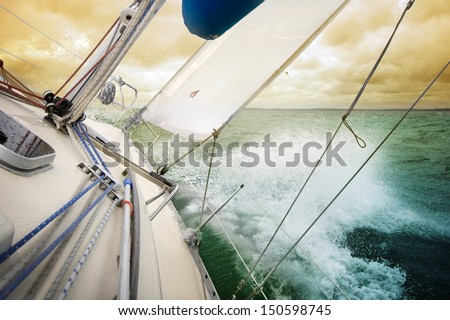 Sailing fast on port tacks with water splashing on deck - stock photo