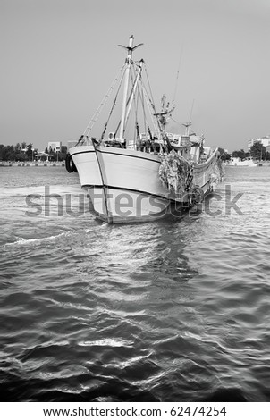 Sailing fishing boat on water of ocean in harbor. - stock photo