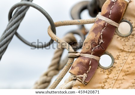 Sailing hardware and canvas sail close up of a vintage sailboat at sea. Selective focus on details - stock photo